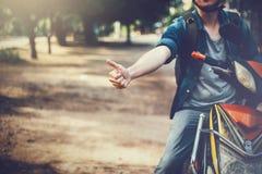 Giovane guida maschio felice e bella del motociclista sulla motocicletta che dà i pollici su e positivo immagine stock libera da diritti