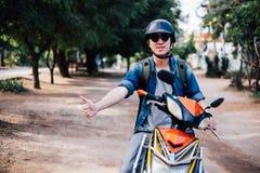 Giovane guida maschio felice e bella del motociclista sulla motocicletta che dà i pollici su e positivo immagini stock libere da diritti