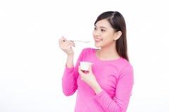 Giovane gusto godente femminile asiatico di yogurt isolato su bianco fotografie stock