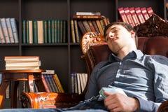 Giovane Guy Sleeping sulla sedia che tiene un libro Fotografia Stock