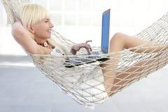 Giovane hammock del computer portatile della ragazza di modo dell'allievo Immagine Stock