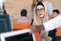 Giovane hijab d'uso arabo della donna di affari, lavorante nel suo ufficio startup immagini stock