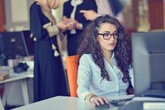 Giovane hijab d'uso arabo della donna di affari, lavorante nel suo ufficio startup Diversità, concetto multirazziale immagine stock