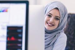 Giovane hijab d'uso arabo della donna di affari, lavorante nella sua partenza immagini stock