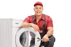 Giovane idraulico che posa da una lavatrice fotografia stock libera da diritti