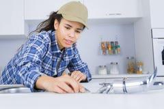 Giovane idraulico femminile che lavora al lavandino immagine stock libera da diritti