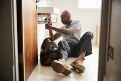Giovane idraulico maschio nero che si siede sul pavimento che ripara un lavandino del bagno, visto dalla entrata, integrale fotografia stock