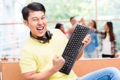 Giovane impiegato cinese felice per il suo riuscito lavoro sul computer immagine stock libera da diritti