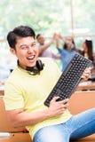 Giovane impiegato cinese felice per il suo riuscito lavoro sul computer immagini stock