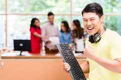 Giovane impiegato cinese felice per il suo riuscito lavoro sul computer fotografia stock