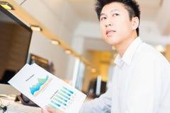 Giovane impiegato di concetto asiatico con i grafici Immagine Stock Libera da Diritti