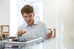 Giovane impiegato di concetto che sorride e che dà una occhiata alla stampante interna 3D Fotografie Stock