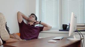 Giovane impiegato di concetto in vetri che si rilassano nell'ufficio con le sue gambe sulla tavola nell'ufficio moderno Rottura d archivi video