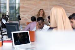 Giovane imprenditore africano frustrato con lo smorfia triste davanti al suo computer portatile in ufficio fotografia stock libera da diritti