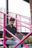 Giovane imprenditore del tipo che lavora fuori facendo uso del computer portatile moderno che si siede sulle scale Concetto di ri fotografie stock