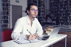 Giovane imprenditore o studente universitario che lavora al computer portatile con il libro sulla tesi scientifica in una bibliot Fotografie Stock