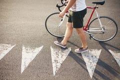 Giovane incrocio dell'uomo di stile dei pantaloni a vita bassa una strada fotografie stock