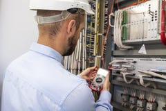 Giovane ingegnere adulto del costruttore dell'elettricista che ispeziona attrezzatura elettrica in contenitore di fusibile di dis fotografia stock