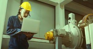 Giovane ingegnere asiatico facendo uso del taccuino vicino a macchinario pesante in fabbrica industriale stock footage