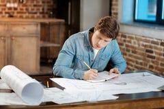 Giovane ingegnere che fa le note per quanto riguarda il suo progetto Immagini Stock Libere da Diritti