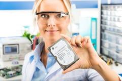 Giovane ingegnere elettronico femminile che giudica HDD disponibile Fotografia Stock Libera da Diritti