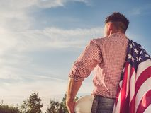 Giovane ingegnere, elmetto protettivo bianco e bandiera americana immagine stock