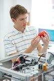 Giovane ingegnere piacevole che controlla pomodoro stampato rosso Fotografia Stock