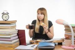 Giovane insegnante affamato che si siede stancamente con un panino e un caffè Fotografia Stock Libera da Diritti