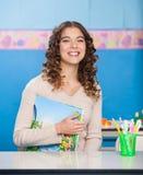 Giovane insegnante With Book Sitting allo scrittorio Immagine Stock Libera da Diritti