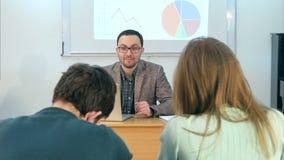 Giovane insegnante che si siede nell'aula della scuola con il computer portatile, parlante con studenti video d archivio