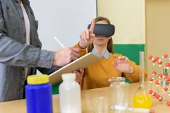 Giovane insegnante che usando i vetri di realtà virtuale e presentazione 3D per insegnare agli studenti nella classe di chimica I fotografie stock
