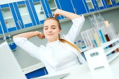 Giovane insegnante di chimica nel posto di lavoro del laboratorio della scuola sonnolento Immagine Stock