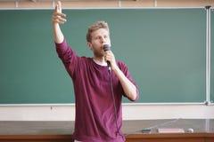 Giovane insegnante di professore che parla con il microfono nel corridoio di conferenza che sta lavagna vicina fotografie stock