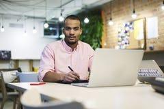 Giovane insegnante e studente che contano somma dei costi e del reddito della sua partenza di affari facendo uso del computer por Fotografia Stock Libera da Diritti