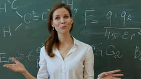 Giovane insegnante femminile attraente dei per la matematica che interagiscono con i suoi giovani studenti della scuola primaria  Fotografie Stock