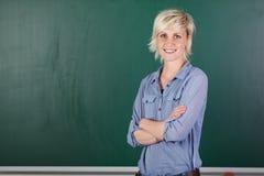 Giovane insegnante femminile sicuro In Front Of Chalkboard Fotografie Stock