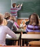 Giovane insegnante maschio che spiega per la matematica alla lavagna Fotografia Stock Libera da Diritti