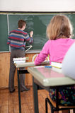 Giovane insegnante maschio che spiega per la matematica alla lavagna Immagini Stock