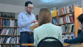 Giovane insegnante maschio con il libro che parla con studenti in biblioteca Fotografia Stock