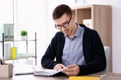 Giovane insegnante maschio con il libro che si siede alla tavola Fotografia Stock Libera da Diritti
