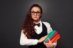 Giovane insegnante in vetri con il mucchio dei libri Fotografie Stock