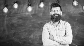 Giovane insegnante vicino alla lavagna nell'aula della scuola L'uomo con la barba ed i baffi sul fronte sorridente stanno davanti Fotografia Stock