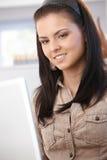 Giovane Internet femminile di ricerca a scansione sul sorridere del computer portatile Fotografia Stock Libera da Diritti