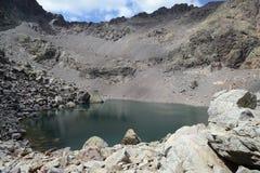 Giovane intestazione turistica al lago della montagna Fotografie Stock