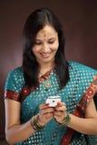Giovane invio di messaggi di testo tradizionale della donna Fotografie Stock Libere da Diritti