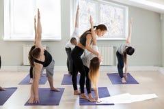 Giovane istruttore femminile di yoga che insegna alla posa di Utthita Trikonasana Fotografia Stock