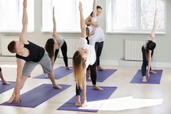 Giovane istruttore femminile di yoga che insegna alla posa di Utthita Trikonasana Fotografie Stock Libere da Diritti
