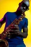 Giovane jazzista afroamericano che gioca il sassofono fotografie stock libere da diritti
