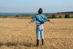 Giovane in jeans, camicia, stivali di gomma nel campo con le sue mani aperte, il concetto di libertà, motivazione, movimento, rit fotografia stock libera da diritti