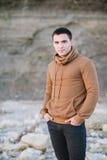 Giovane in jeans neri ed in un saltatore marrone Fotografia Stock